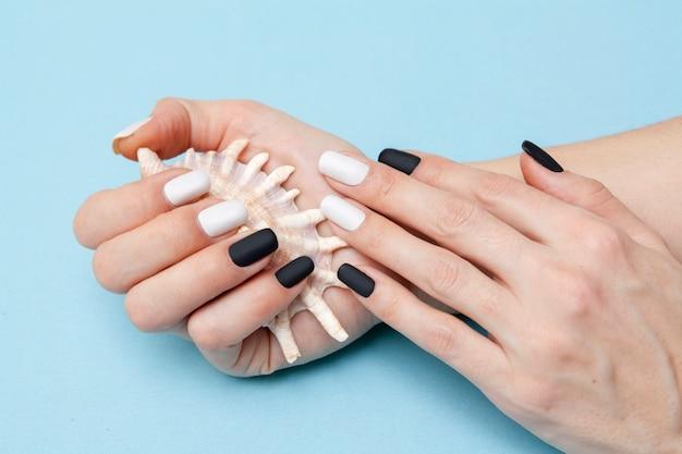 Preto e branco manicure fosco na mão de uma mulher em uma superfície azul
