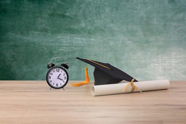 Preto graduado cap, certificado de grau e despertador ritmo em fundo de madeira