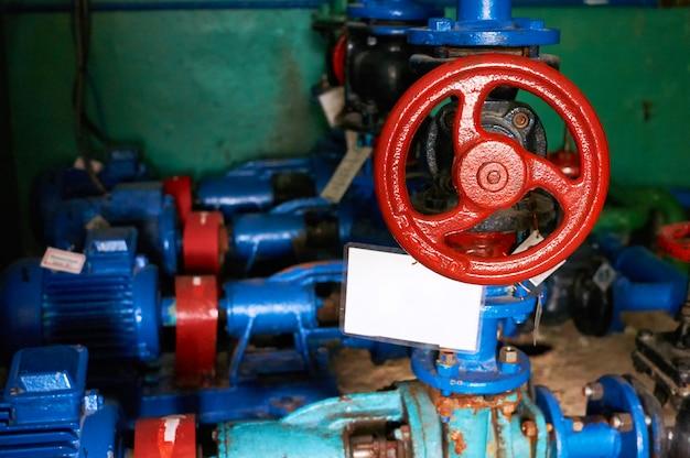Preto mais velho com alças de trava vermelha na tubulação de água fria colorida em azul.
