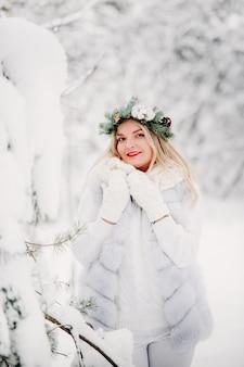 Pretrato de uma mulher com roupas brancas em uma floresta fria de inverno. menina com uma coroa na cabeça em uma floresta de inverno coberto de neve.