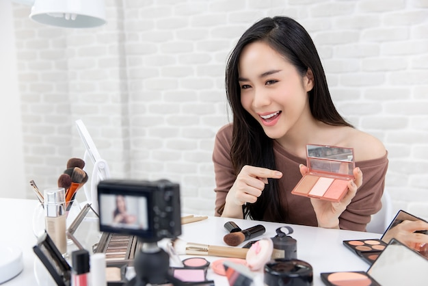 Pretty asian blogger fazendo um vídeo de demonstração sobre cosméticos e maquiagem.