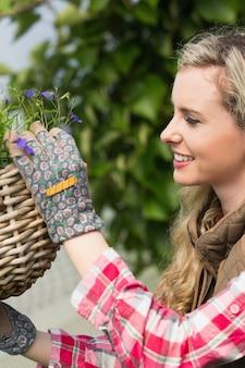 Pretty blond colocando uma cesta de flores pendurada