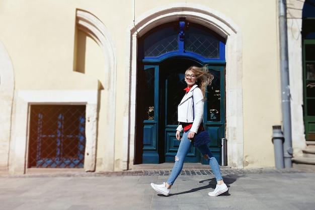 Pretty blond girl with jeans and white jacket anda ao longo da rua
