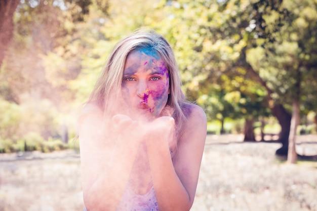 Pretty blonde blowing powder paint
