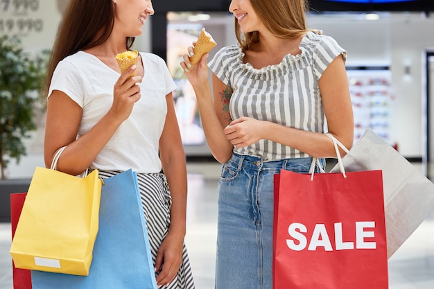 Pretty girls shopping in mall à venda