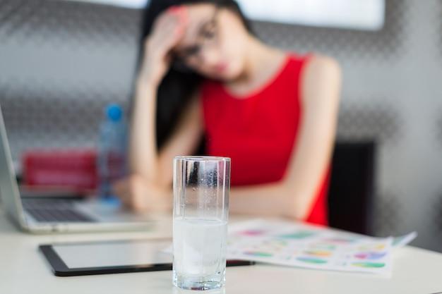 Pretty, jovem businesslady em vestido vermelho e óculos sentar à mesa e trabalhar