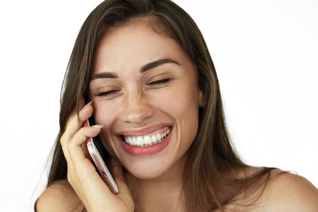 Pretty laughing woman fala no telefone de pé no fundo branco