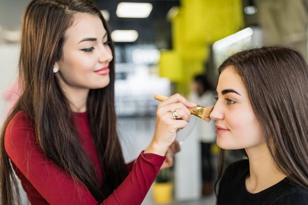 Pretty master está fazendo maquiagem natural para modelo bonita em salão de beleza