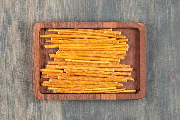 Pretzel salgado espetado em prato de madeira
