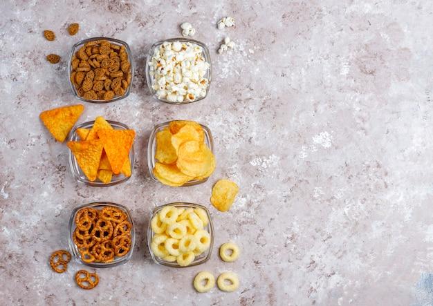 Pretzels, batatas fritas, biscoitos e pipoca em tigelas