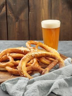 Pretzels de sal marinho na mesa com um copo de cerveja light