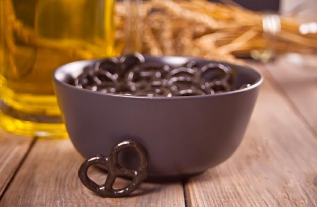 Pretzels pretos pequenos em uma tigela com cerveja de vidro ob na mesa de madeira.