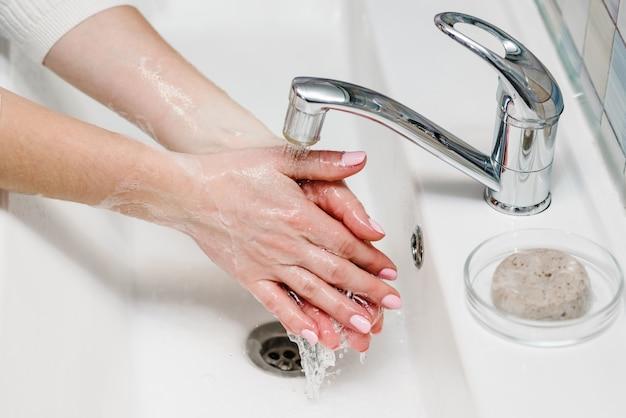 Prevenção contra coronavírus. lave as mãos com sabão antibacteriano e água quente corrente, esfregando as unhas e os dedos na pia. lavar as mãos. epidemia covid-19. prevenção da doença da gripe.