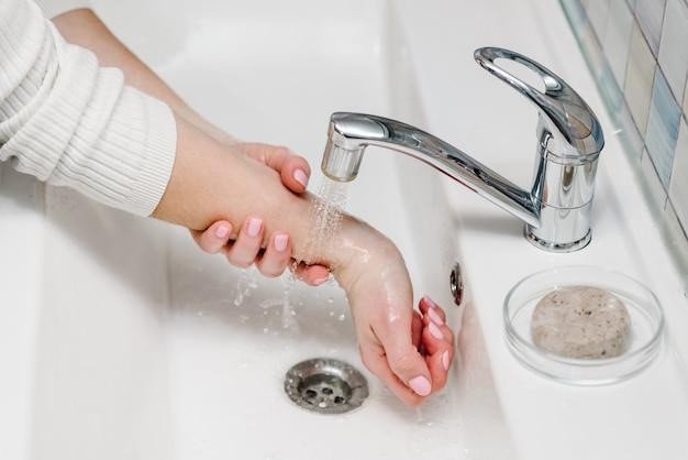 Prevenção contra coronavírus. lave as mãos com sabão antibacteriano e água quente corrente, esfregando as unhas e os dedos na pia