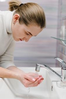Prevenção contra coronavírus. lave o rosto com sabão antibacteriano e água corrente na pia