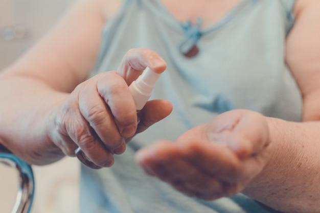 Prevenção da doença de coronavírus covid-19. mulher velha usar um desinfetante para as mãos à base de álcool com álcool a 60%, as mãos fechem. como se preparar para o coronavírus