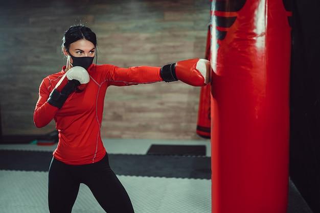 Prevenção de coronavírus covid-19, luta. menina com uma máscara médica e luvas de boxe. combate a vírus.