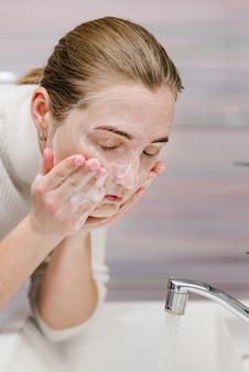 Prevenção de coronavírus. lave o rosto com sabão antibacteriano, água corrente na pia. lavando o rosto. epidemia covid-19. higiene corporal da prevenção de coronavírus. doença da gripe.