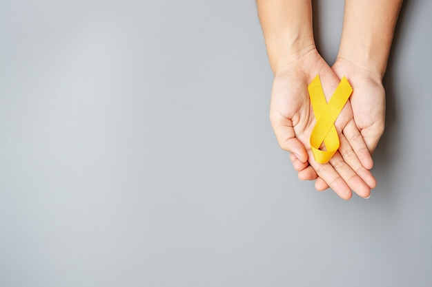 Prevenção de suicídio, sarcoma, osso, bexiga, mês de conscientização do câncer infantil, fita amarela para apoio a pessoas que vivem e adoecem. conceito do dia mundial da saúde das crianças e do câncer