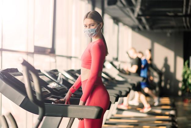 Prevenção do coronavírus covid-19, garota fitness com uma máscara médica, posando no ginásio. vírus de combate.