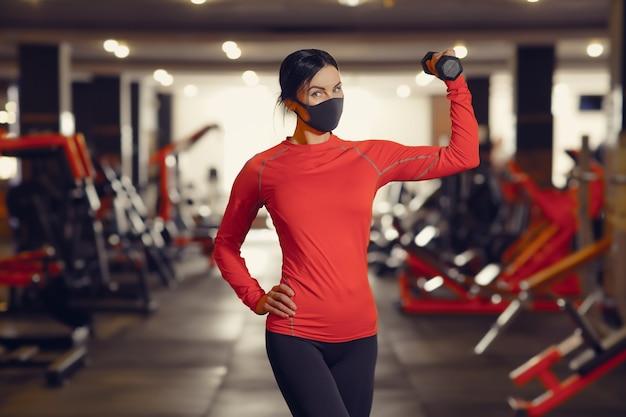 Prevenção do coronavírus covid-19, garota fitness com uma máscara médica segurando um haltere