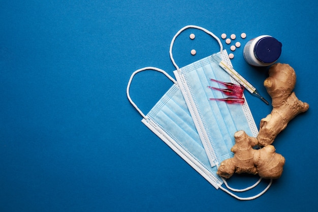 Previna o coronavírus. máscara médica, termômetro, vitaminas, seringa sobre fundo azul.