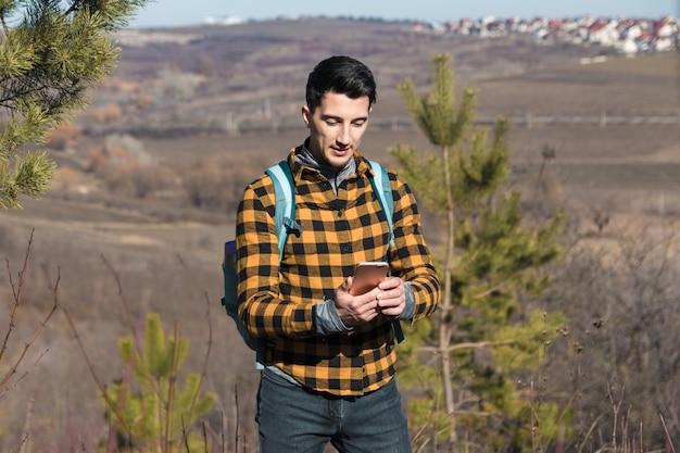 Primavera ao ar livre. homem bonito na zona rural, usando o telefone para navegar