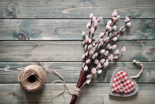 Primavera com monte de salgueiro e coração de madeira em madeira rústica