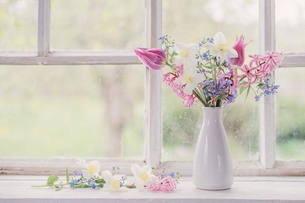 Primavera flores em um vaso branco no peitoril da janela antiga