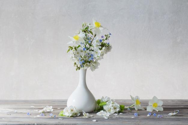 Primavera flores em um vaso na mesa de madeira