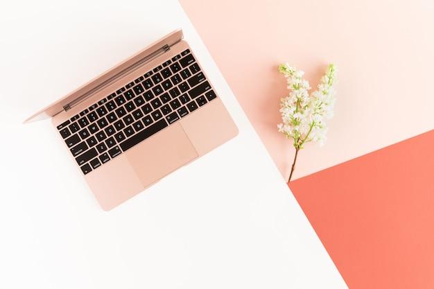 Primavera flores lilás e rosa ar laptop na mesa pastel feminina.