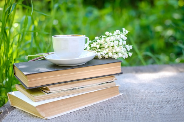 Primavera flores lírios do vale e uma xícara de chá em uma pilha de livros antigos