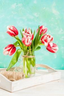 Primavera . floresce tulipas em um frasco de vidro, em uma luz - azul e branco de madeira.
