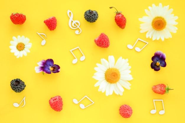 Primavera fundo clave de sol e notas musicais com flores e frutos em um fundo amarelo.