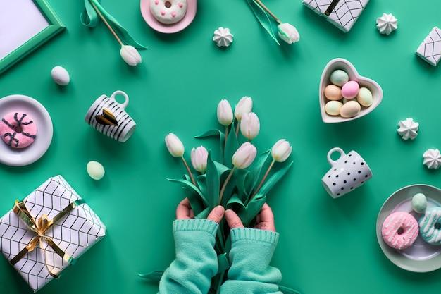 Primavera geométrica plana leigos em branco e verde na parede rosa páscoa, dia das mães, aniversário de primavera ou aniversário. lightboard plástico calor, ovos de páscoa, cafeteira, copos, tulipas, presentes.