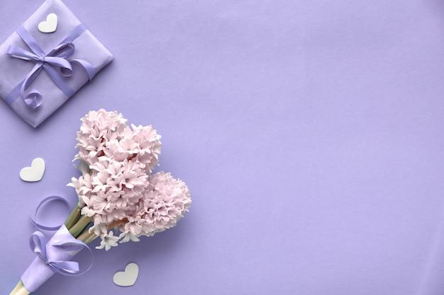 Primavera lilás parede colorida com jacinto rosa e caixa de presente embrulhada, cópia-espaço