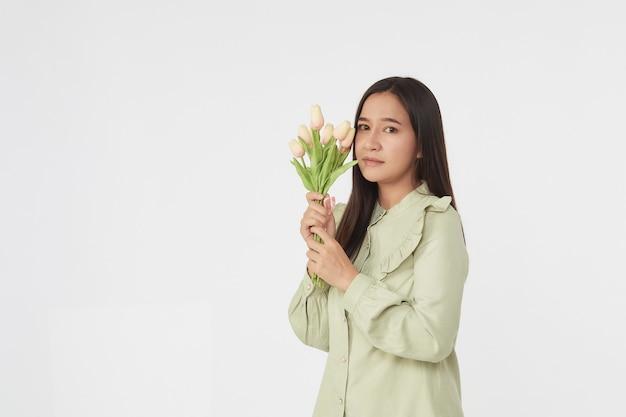 Primavera linda menina alegre sorrindo e segurando um buquê de flores de tulipa. mulher asiática feliz nova.