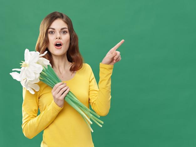 Primavera linda menina com flores em um fundo colorido, mulher posando com um buquê de flores, dia da mulher