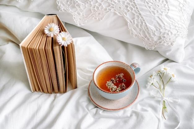 Primavera natureza morta com uma xícara de chá de ervas naturais e flores de camomila e margarida.