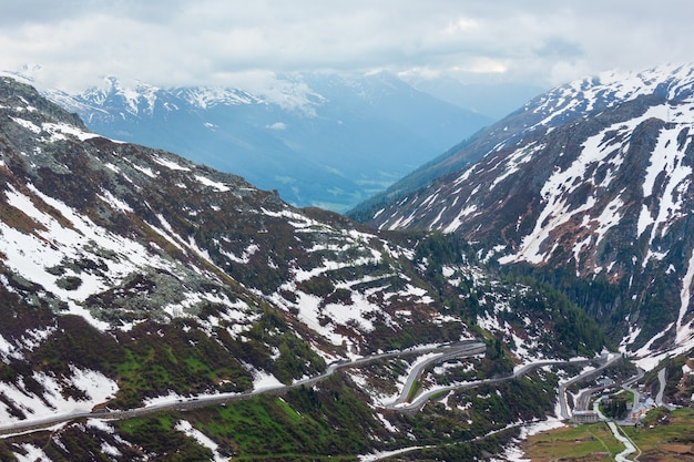 Primavera nublado paisagem montanhosa com estrada serpentina em furka pass, suíça.