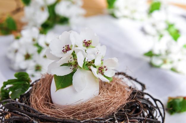 Primavera páscoa composição de flores em um ovo branco em um ninho de galhos na toalha de mesa cinza.