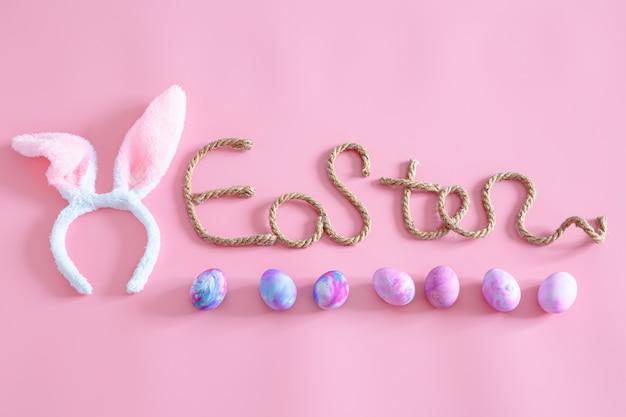 Primavera páscoa festiva. inscrição criativa de páscoa em rosa com itens de decoração de páscoa.