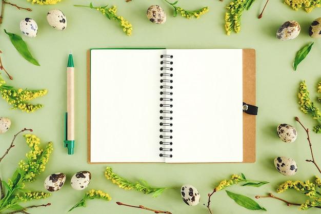 Primavera páscoa floral frame e notebook. galhos de árvores naturais, flores amarelas, ovos de codorna, bloco de notas em branco aberto no verde