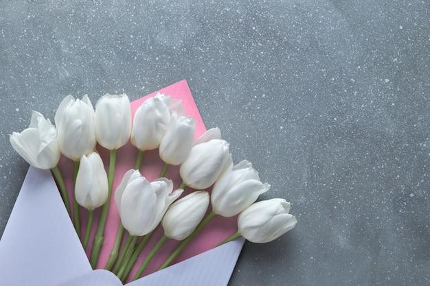 Primavera plana leigos, tulipas brancas em envelope branco e rosa