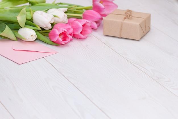 Primavera tulipas cor de rosa, caixa de presente e cartão de papel vazio. conceito de dia das mães