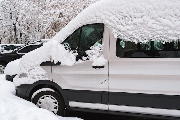 Primeira nevasca. carros cobertos de neve após uma nevasca repentina. inverno na cidade