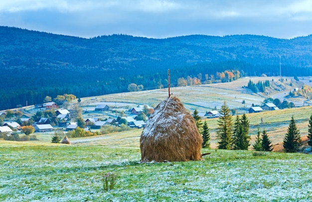 Primeira neve de inverno em outubro no planalto das montanhas dos cárpatos, com vila e rodovia distantes