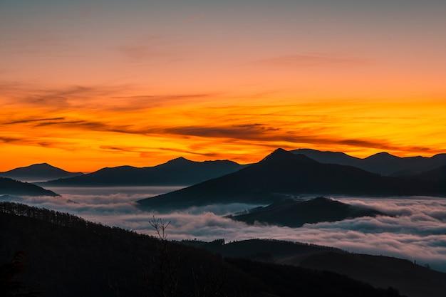 Primeiras luzes nas montanhas com nevoeiro