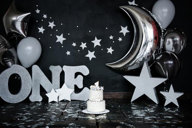 Primeiro bolo branco do aniversário com estrelas e vela para o bebé pequeno e decorações para a quebra do bolo.