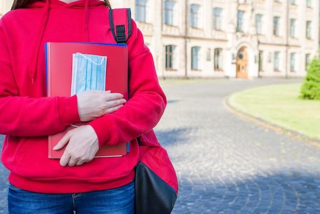 Primeiro dia na escola após o conceito de universidade. foto de close-up recortada de uma adolescente em um suéter vermelho casual segurando livros e uma máscara médica em pé perto de portas.